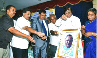 Dr. Wooday P. Krishna, Chairman, Gandhi Peace Foundation offering floral tributes to Backward Classes Leader D. Devaraj Urs on his birth anniversary, 2015, at a public function organized by Urs Vedike in Bengaluru, 2015.